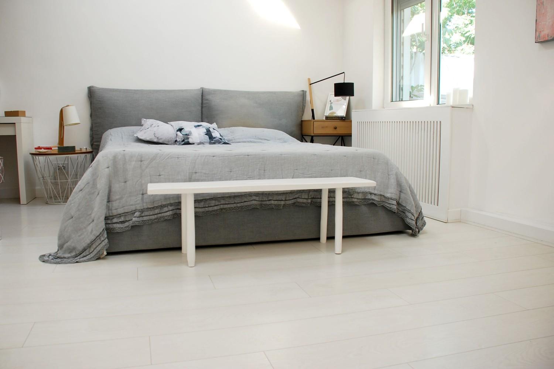 dormitor cu parchet alb și pat gri