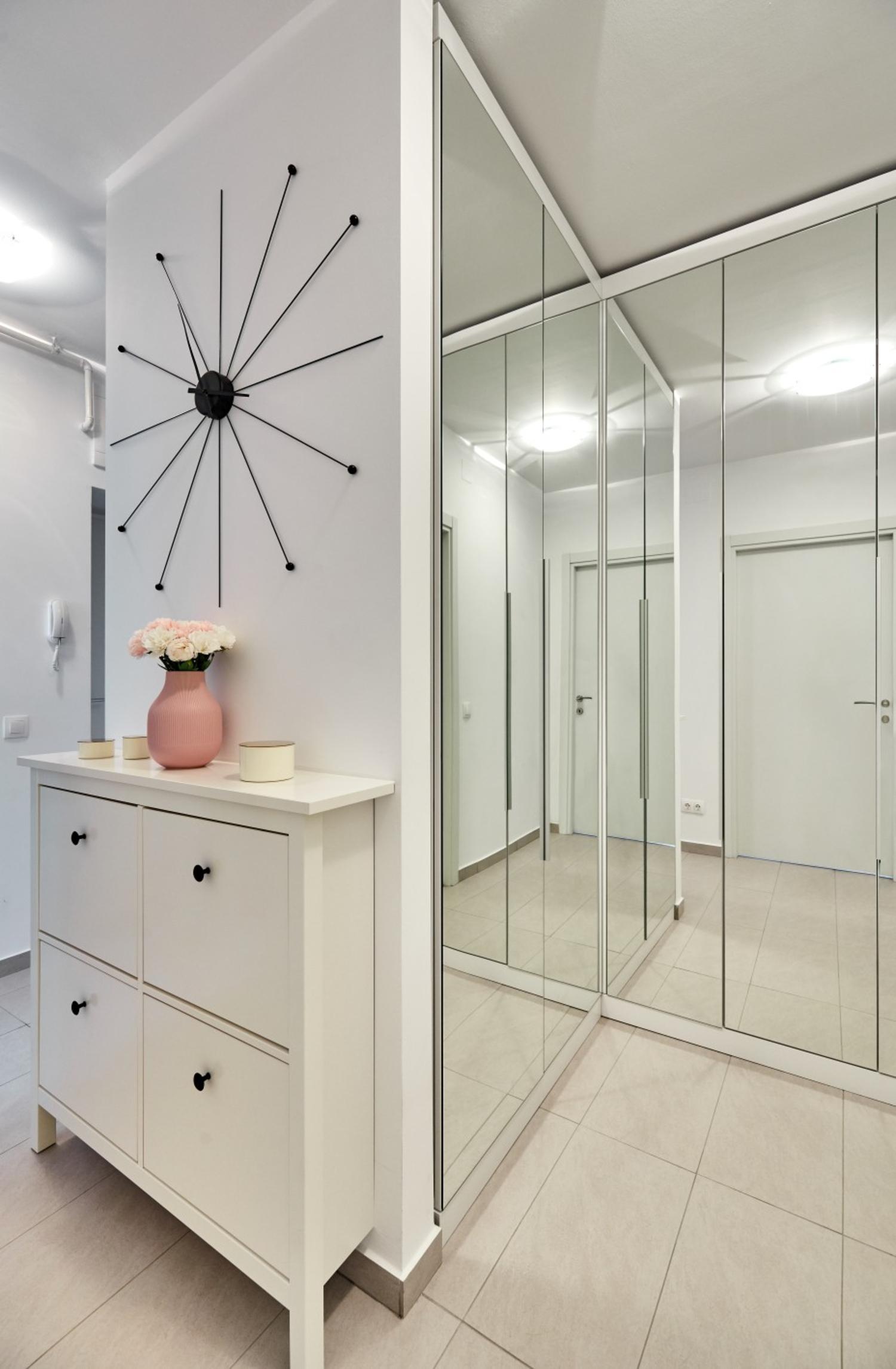 Dulap în formă de L placat cu oglinzi. Amenajare apartament două camere București, arh. int. Cristina Micu.