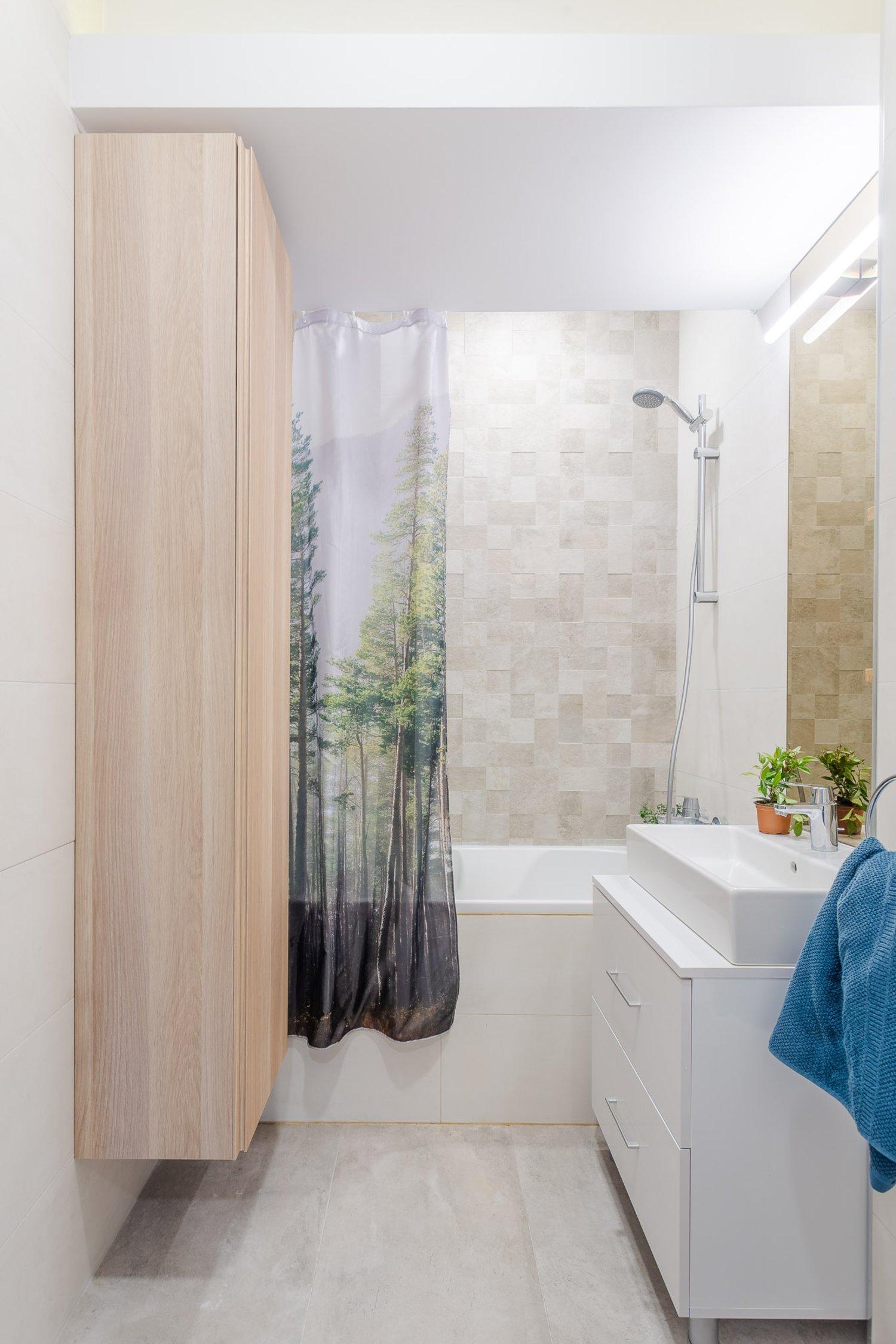 Amenajare apartament de burlac - baie minimalistă, mobilier alb, perdea de duș, dulap suspendat
