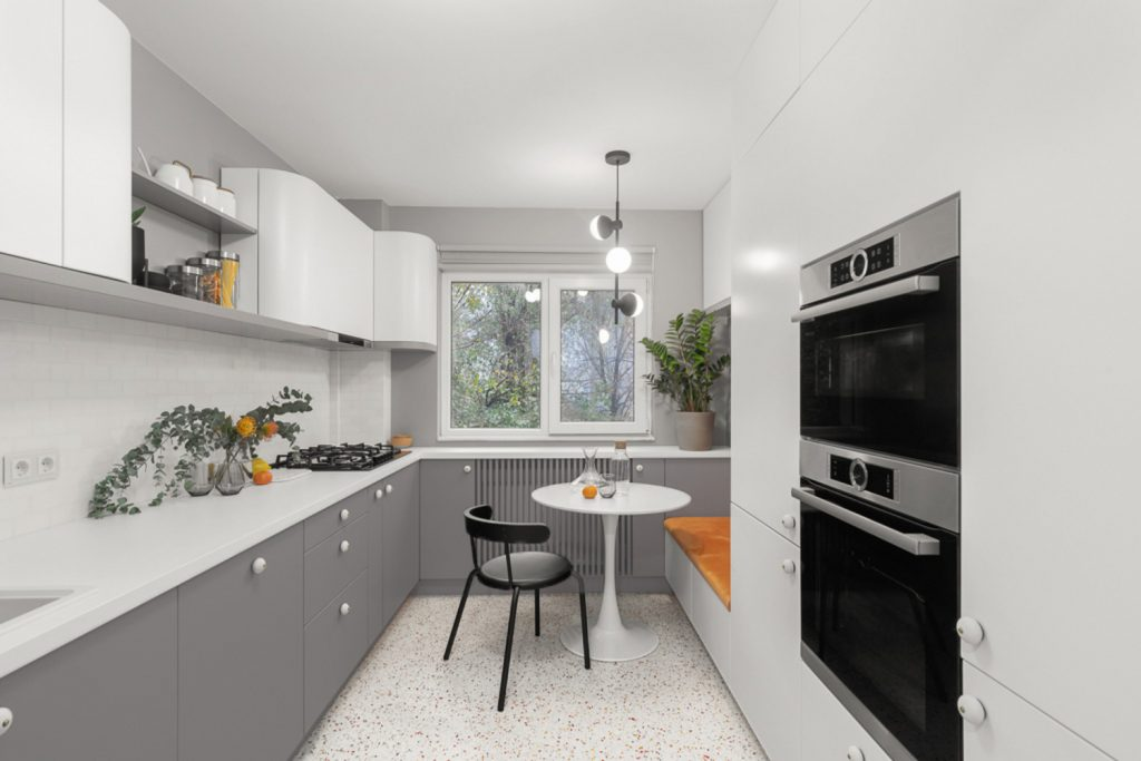Amenajare bucătărie cu mobilier rotunjit alb și gri
