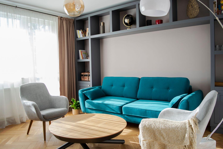 Apartament patru camere Cluj - living gri canapea albastra, masa extensibila pentru jocuri
