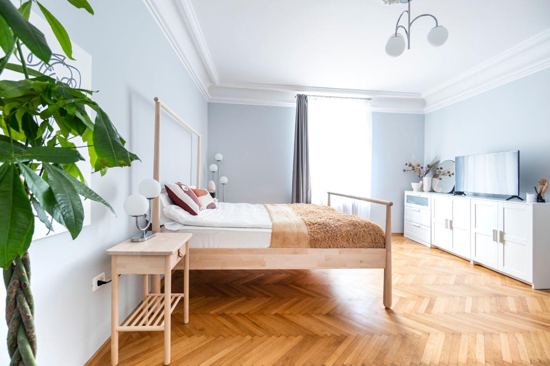 Dormitorul e amenajat minimalist, cu un pat cu baldachin IKEA și o comodă albă.